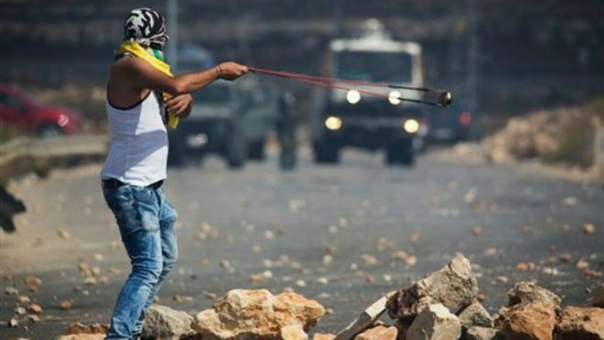 Sept. 29, 2015: A Palestinian demonstrator readies to hurl a stone during clashes with Israeli troops near Ramallah, West Bank. Palestinian demonstrators clashed with Israeli troops across the West Bank on Tuesday as tensions remained high following days of violence at Jerusalem's most sensitive holy site.