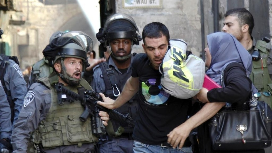 An Israeli border policeman confronts a Palestinian man during confrontations in the Old City of Jerusalem, Monday, Sept. 28, 2015. Palestinians clashed with Israeli riot police after barricading themselves in a mosque at Jerusalem's most sensitive holy site, throwing firebombs and rocks at officers outside during a major Jewish holiday on Monday. The hilltop compound in Jerusalem's Old City is a frequent flashpoint and its fate is a core issue at the heart of the Israeli-Palestinian conflict. (AP Photo/Mahmoud Illean)