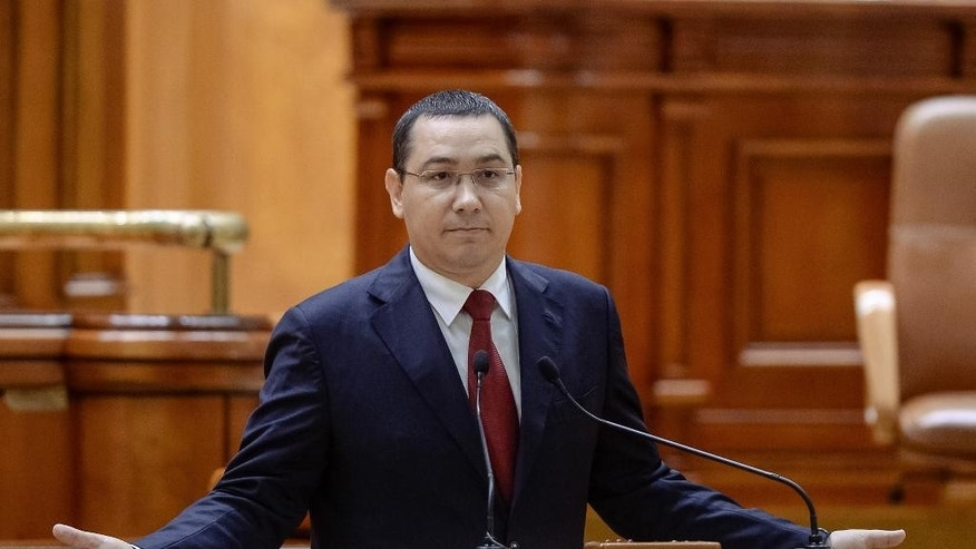 Romania's prime minister Victor Ponta gestures during a special parliament session in Bucharest, Romania,Tuesday, Sept. 29, 2015, before facing a no-confidence vote. Romania's parliament on Tuesday debated a vote of no confidence against the prime minister, a week after he went on trial for corruption charges including tax evasion, money laundering, conflict of interest and making false statements while he was working as a lawyer in 2007 and 2008. (Octav Ganea/Mediafax via AP) ROMANIA OUT