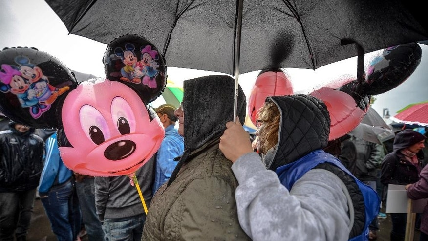 A protester shelters from the rain under an umbrella holding an inflatable Mickey Mouse, a cartoon character traditionally associated by protesters to the country's premier, during a demonstration against Romania's Prime Minister Victor Ponta outside the Romanian Parliament in Bucharest, Romania, Tuesday, Sept. 29, 2015. Romania's parliament on Tuesday debated a vote of no confidence against the prime minister, a week after he went on trial for corruption charges including tax evasion, money laundering, conflict of interest and making false statements while he was working as a lawyer in 2007 and 2008. (Andreea Alexandru/Mediafax via AP) ROMANIA OUT