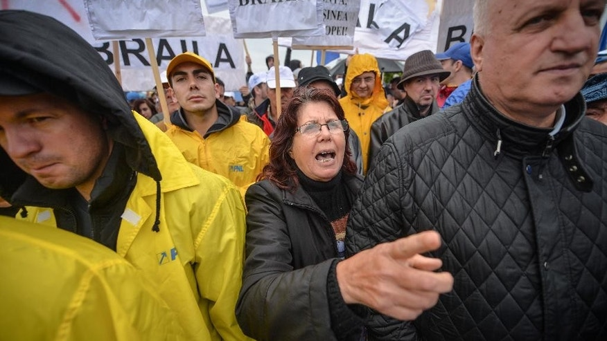 A woman shouts slogans against Romania's Prime Minister Victor Ponta during a protest outside the Romanian Parliament  in Bucharest, Romania, Tuesday, Sept. 29, 2015. Romania's parliament on Tuesday debated a vote of no confidence against the prime minister, a week after he went on trial for corruption charges including tax evasion, money laundering, conflict of interest and making false statements while he was working as a lawyer in 2007 and 2008. (Andreea Alexandru/Mediafax via AP) ROMANIA OUT
