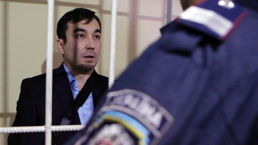 "Russian special forces captain Yevgeny Yerofeyev stands in a cage during a trial hearing at the Holosiivskyi District Court in Kiev, Ukraine, on Tuesday, Sept. 29, 2015. Russians Alexander Alexandrov and Yevgeny Yerofeyev were captured by Ukraine's forces in mid-May in the Lugansk region, in eastern Ukraine. Kiev has claimed that the detainees are Russian servicemen, while Russia's Defense Ministry has said the Russians ""were not active servicemen of Russia's"". (AP Photo/Sergei Chuzavkov)"