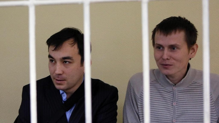 Russian special forces captain Yevgeny Yerofeyev, left, and Sgt. Alexander Alexandrov, captured while fighting in war-torn eastern Ukraine, sit in a cage during a trial hearing at the Holosiivskyi District Court in Kiev, Ukraine, on Tuesday, Sept. 29, 2015. (AP Photo/Sergei Chuzavkov)