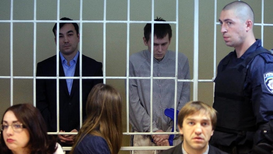 "Russian special forces captain Yevgeny Yerofeyev, left, and Sgt. Alexander Alexandrov stand in a cage during a trial hearing at the Holosiivskyi District Court in Kiev, Ukraine, on Tuesday, Sept. 29, 2015.  Russians Alexander Alexandrov and Yevgeny Yerofeyev were captured by Ukraine's forces in mid-May in the Lugansk region, in eastern Ukraine. Kiev has claimed that the detainees are Russian servicemen, while Russia's Defense Ministry has said the Russians ""were not active servicemen of Russia's"". (AP Photo/Sergei Chuzavkov)"