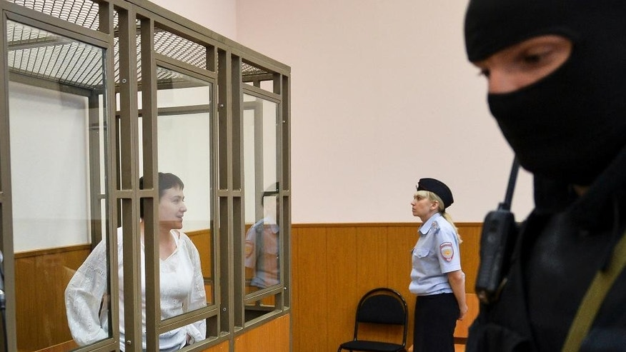 Ukrainian jailed military officer Nadezhda Savchenko, left, stands in a cage during a court hearing in a town of Donetsk, Rostov-on-Don region, Russia, on Tuesday, Sept. 29, 2015. The Russian court has begun hearing the high-profile case against Ukrainian officer Nadezhda Savchenko, who is charged in the deaths of two Russian journalists in eastern Ukraine. Russian investigators allege that Savchenko, who served in a volunteer battalion fighting with government troops against Russia-backed rebels, provided the coordinates for a mortar attack that killed the journalists in June 2014. (AP Photo)