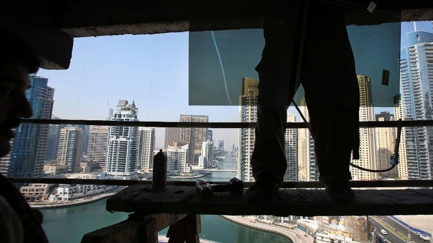 In this Monday, Aug. 10, 2015 photo, workers fix a window glass at an under-construction high rise located in the Marina Waterfront, in Dubai, United Arab Emirates. The United Arab Emirates is introducing labor reforms that aim to tighten oversight of employment agreements for the millions of temporary migrant workers that comprise the bulk of the country's workforce, a top Emirati official said Tuesday. (AP Photo/Kamran Jebreili)