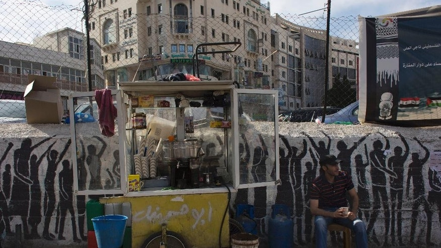 A Palestinian drink vendor drinks coffee and smokes a cigarette while he waits for customers in the West Bank city of Ramallah, Tuesday, Sept. 29, 2015. The World Bank said the Palestinian economy has worsened for a third consecutive year. In a report released on Monday, the World Bank cited a number of factors, including reduced donor aid, Israeli restrictions and political instability that has deterred investors. (AP Photo/Nasser Nasser)