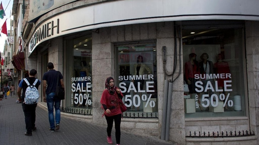 Palestinian walk past a boutique in the West Bank city of Ramallah, Tuesday, Sept. 29, 2015. The World Bank said the Palestinian economy has worsened for a third consecutive year. In a report released on Monday, the World Bank cited a number of factors, including reduced donor aid, Israeli restrictions and political instability that has deterred investors. (AP Photo/Nasser Nasser)