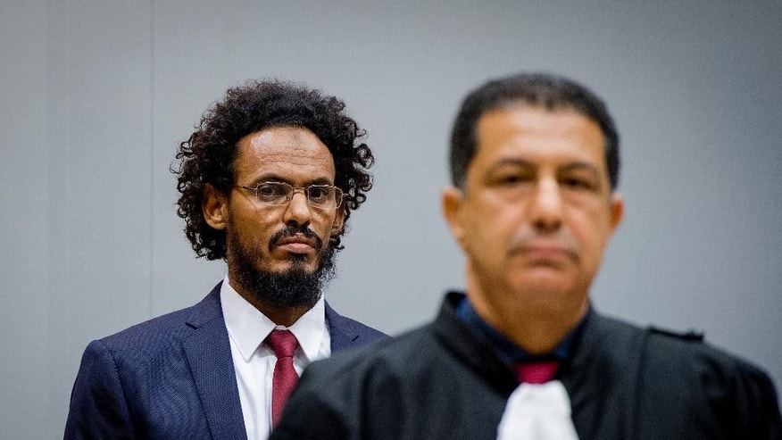 Ahmad Al Mahdi Al Faqi, left, enters the court room of the International Criminal Court in The Hague, Netherlands, Wednesday, Sept. 30, 2015. Al Faqi, an alleged Islamic radical, is the first suspect in the court's custody charged with the war crime of deliberately attacking and destroying religious or historical monuments in Timbuktu, Mali. (AP Photo/Robin van Lonkhuijsen, Pool)