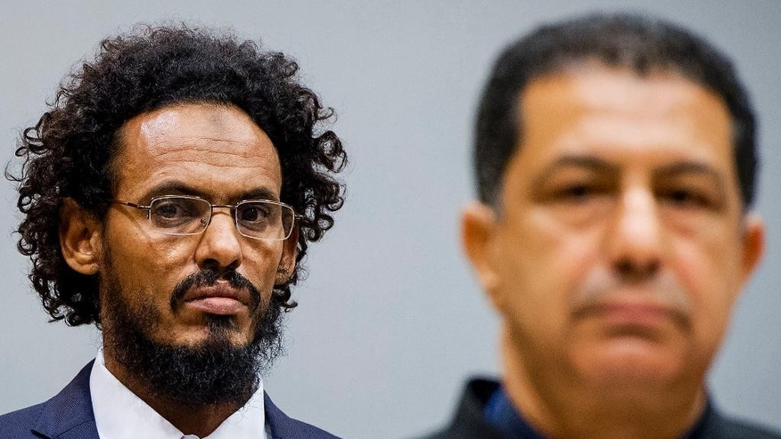Ahmad Al Mahdi Al Faqi, left, enters the court room for his initial appearance at the International Criminal Court in The Hague, Netherlands, Wednesday, Sept. 30, 2015. Al Faqi, an alleged Islamic radical, is the first suspect in the court's custody charged with the war crime of deliberately attacking and destroying religious or historical monuments in Timbuktu, Mali. (AP Photo/Robin van Lonkhuijsen, Pool)