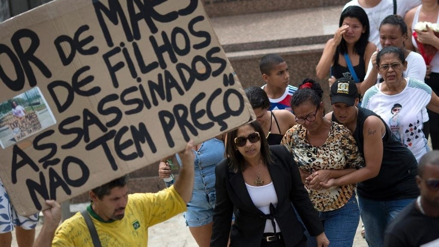 "A man holds a sign that reads in Portuguese; ""The sadness of mothers of children killed, doesn't have a price,"" as relatives and friends of Eduardo Felipe Santos Victor, a teenager who was shot dead at Morro da Providencia favela, walk to his burial service, in Rio de Janeiro, Brazil, Wednesday, Sept. 30, 2015. Five Brazilian police officers have been taken into custody for allegedly altering a crime scene by placing a gun in the hand of the seventeen-year-old, after they allegedly killed him during a shootout in a Rio de Janeiro. As he lay dying in a pool of blood, a slum resident shot video of one of the officers firing a handgun into the air and then putting the gun in Victor's hand. (AP Photo/Silvia Izquierdo)"