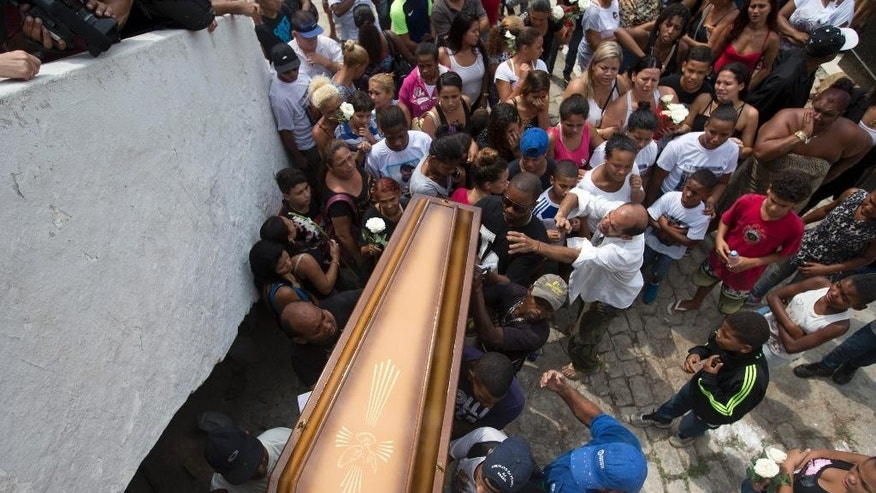 Relatives and friends carry the coffin containing the remains of Eduardo Felipe Santos Victor, a teenager who was shot dead at Morro da Providencia favela, in Rio de Janeiro, Brazil, Wednesday, Sept. 30, 2015. Five Brazilian police officers have been taken into custody for allegedly altering a crime scene by placing a gun in the hand of the seventeen-year-old, after they allegedly killed him during a shootout in a Rio de Janeiro. As he lay dying in a pool of blood, a slum resident shot video of one of the officers firing a handgun into the air and then putting the gun in Victor's hand. (AP Photo/Silvia Izquierdo)