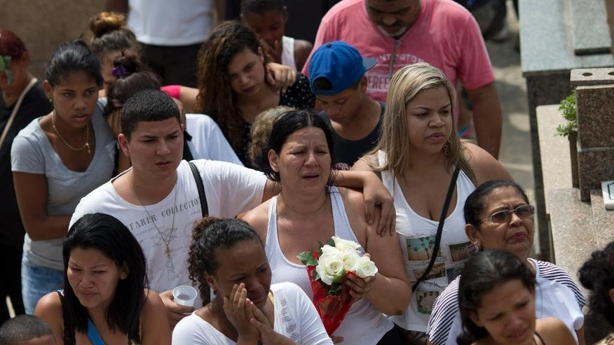 Relatives and friends of Eduardo Felipe Santos Victor, a teenager who was shot dead at Morro da Providencia favela, attend his burial service, in Rio de Janeiro, Brazil, Wednesday, Sept. 30, 2015. Five Brazilian police officers have been taken into custody for allegedly altering a crime scene by placing a gun in the hand of the seventeen-year-old, after they allegedly killed him during a shootout in a Rio de Janeiro. As he lay dying in a pool of blood, a slum resident shot video of one of the officers firing a handgun into the air and then putting the gun in Victor's hand. (AP Photo/Silvia Izquierdo)