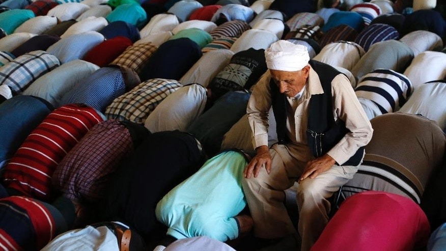 A muslim elderly man prays as he sits on a small stool, with other faithful from the  Turkish Cypriot northern third of ethnically divided Cyprus visit the Halal Sultan Tekke, one of Islam's most important holy places, near Larnaca in the  Greek Cypriot south on Wednesday, Sept. 30, 2015. The visit to the Tekke, where according to tradition the Prophet Mohammed's foster mother is buried, took place as part of the Muslim feast of Eid al-Adha . (AP Photo/Petros Karadjias)