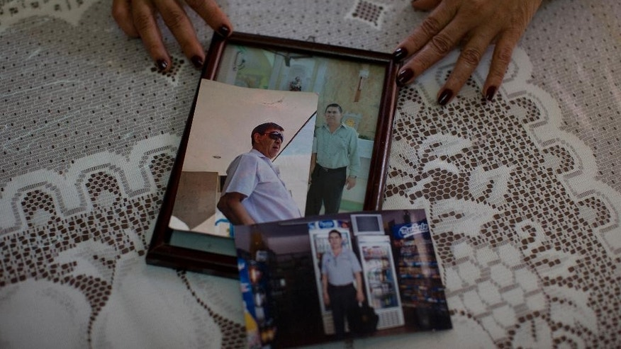 In this June 17, 2015 photo, Yolanda Alvarez Antunez shows photos of her husband, Luis Alberto Castillo, during an interview at her home in Ahuehuepan, Mexico. On the morning of Jan. 10, 2013, Yolanda headed to Iguala to see if the public hospital had an appointment yet to treat her husband's diabetic retinopathy. Luis Alberto stayed behind in Ahuehuepan to tend their small grocery store. That's when a red pickup pulled up out front, and one of the men burst in, ordering Luis Alberto to come with them. (AP Photo/Dario Lopez-Mills)