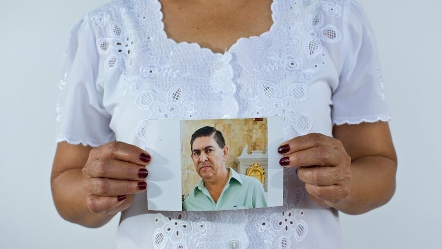 In this June 2, 2015 photo, Yolanda Alvarez Antunez holds up an image of her husband, Luis Alberto Ramirez Castillo, in Iguala, Mexico. Her husband was 54 years old when he was kidnapped by armed men outside of his home on Jan. 10, 2013. While trying to pay for the ransom, Yolanda herself was taken by the kidnappers and had to pay extra to be freed. (AP Photo/Dario Lopez-Mills)
