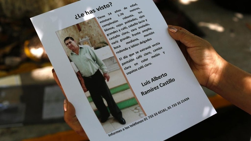 In this Aug. 25, 2015 photo, Yolanda Alvarez Antunez shows a copy of the leaflets she has been posting in the streets seeking information about her missing husband, who was kidnapped two years ago, in Iguala, Mexico. Beto, as he was called, was broad and tall, still strong at the age of 54. Rumored sightings of her husband reach her from time to time.  (AP Photo/Dario Lopez-Mills)