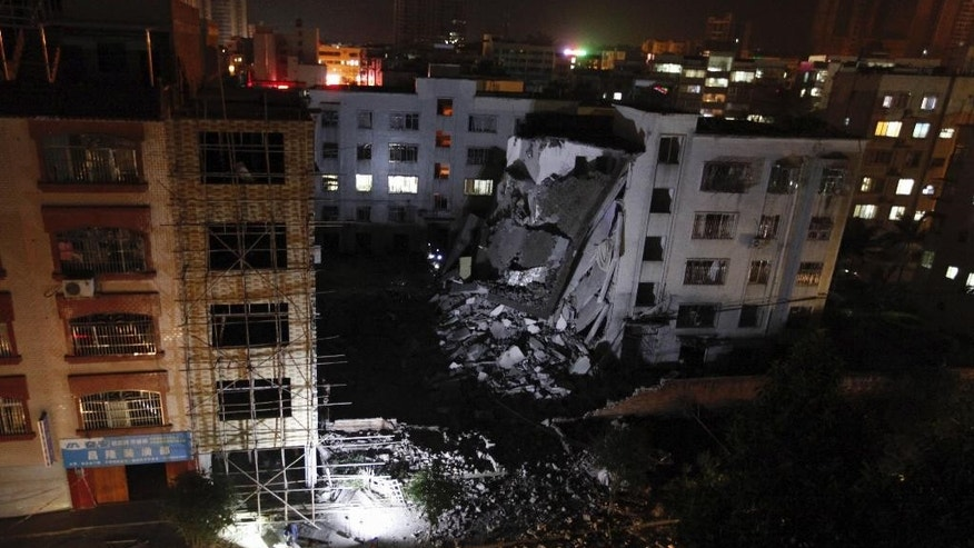A view of a residential building partially collapsed by what police are describing as explosive devices delivered in mail packages in Liucheng county in south China's Guangxi Zhuang Autonomous Region Wednesday Sept. 30, 2015. A 33-year-old local resident was identified as a suspect after a series of explosions targeting public buildings in a small city in southern China killed several people and injured dozens on Wednesday, officials and state media said.(Chinatopix Via AP) CHINA OUT