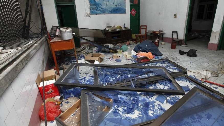 A room in a neighboring building is damaged by the shockwave of an explosion that partially collapsed a residential building in Liucheng county in south China's Guangxi Zhuang Autonomous Region Wednesday Sept. 30, 2015. A 33-year-old local resident was identified as a suspect after a series of explosions targeting public buildings in a small city in southern China killed several people and injured dozens on Wednesday, officials and state media said.(Chinatopix Via AP) CHINA OUT