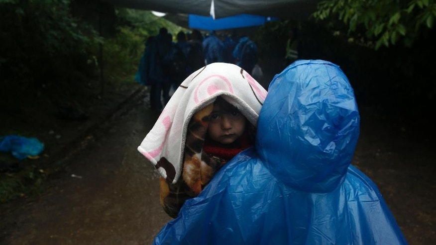 A group of migrants head to cross a border line between Serbia and Croatia, near the village of Berkasovo, about 100 km west from Belgrade, Serbia, Tuesday, Sept. 29, 2015. Asylum seekers are slogging through rain and mud-caked roads in Croatia, as autumnal conditions worsen on their journeys to seek sanctuary in richer European countries. (AP Photo/Darko Vojinovic)