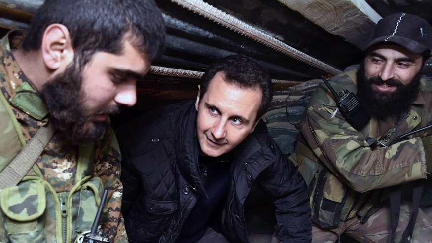 FILE - In this Wednesday, Dec. 31, 2014, file photo released by the Syrian official news agency SANA, Syrian President Bashar Assad, center, speaks with Syrian troops during his visit to the front line in the eastern Damascus district of Jobar, Syria.
