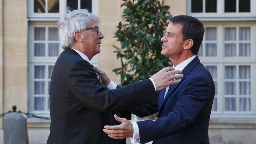 European Commission President Jean-Claude Juncker, left, is welcomed by French Prime Minister Manuel Valls, right, at the Hotel Matignon in Paris, France, Tuesday, Sept. 29, 2015. French Prime Minister Manuel Valls and European Commission President Jean-Claude Juncker discussed on Tuesday the economic situation in France. (AP Photo/Michel Euler)