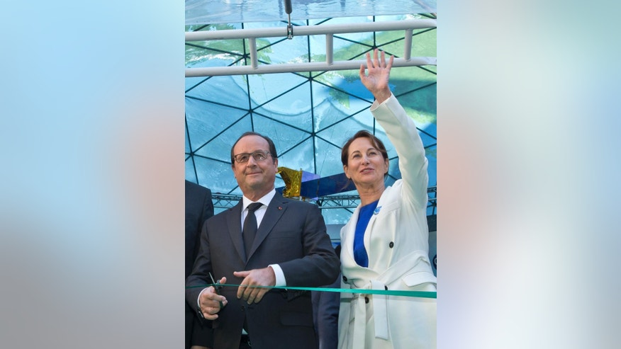 France's President Francois Hollande, left, cuts a ribbon during an inauguration ceremony of an exhibition on climate, while Environment Minister Segolene Royal, right,  waves as she stands next to him, at the environment ministry in Paris, France, Wednesday, Sept. 30, 2015. The exhibition who promote the Climate Change Conference 2015,  is organized by the French government. (AP Photo/Michel Euler, Pool)