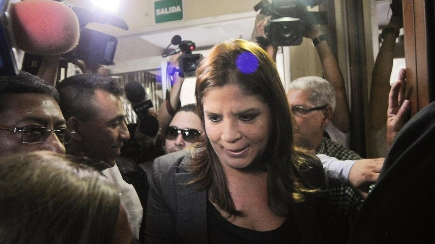 FILE - In this July 3 2015, file photo, National Congress Vice President and member of the ruling National Party Lena Gutierrez, is swarmed by media as she voluntarily arrives at the Supreme Court to answer for the alleged crimes of falsifying documents, and against public health, in Tegucigalpa, Honduras. The formal trial against Gutierrez opened Wednesday, Sept. 30, 2015, in a medical sales scandal that has rocked Honduras and led to mass protests against corruption and impunity. (AP Photo/Fernando Antonio, File)