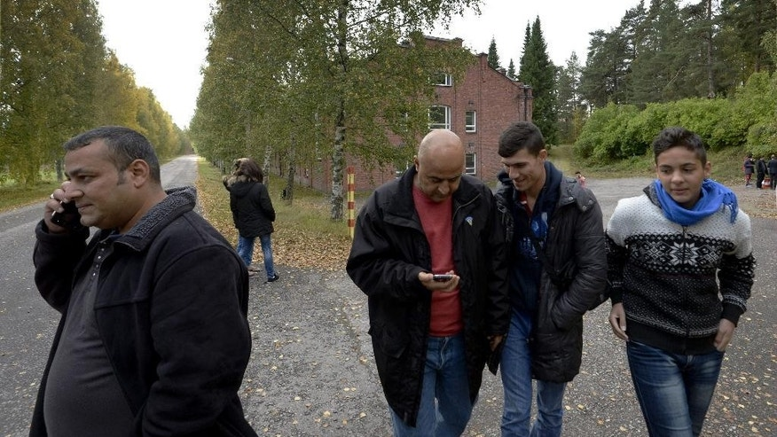 In this photo taken Friday, Sept. 25, 2015, Iraqi asylum seekers stand outside a refugee center located in the former army barracks, Lahti, Finland. Finland, on the northeastern frontier of the EU with vast expanses of forests and reindeer roaming the wilds of Lapland, with long, dark, cold winters, has not been a prime destination for population flows in Europe, but now hundreds of people are crossing daily from neighboring Sweden after traveling through that country by train or bus. (Markku Ulander/Lehtikuva via AP) FINLAND OUT, NO SALES
