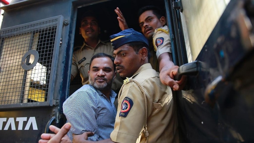 One of the men accused in the 2006 Mumbai train bombings is escorted by policemen from a prison to a court in Mumbai, India, Wednesday, Sept. 30, 2015. An Indian court has sentenced five suspected Islamic militants to death and given seven others life in prison for bombing attacks nine years ago on seven Mumbai commuter trains that killed 188 people and wounded more than 800. (AP Photo/Rafiq Maqbool)