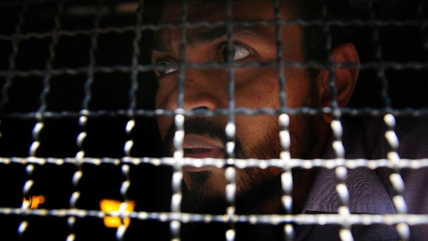 One of the men accused in the 2006 Mumbai train bombings looks from a police van as he is taken from a prison to a court in Mumbai, India, Wednesday, Sept. 30, 2015. An Indian court has sentenced five suspected Islamic militants to death and given seven others life in prison for bombing attacks nine years ago on seven Mumbai commuter trains that killed 188 people and wounded more than 800. (AP Photo/Rafiq Maqbool)