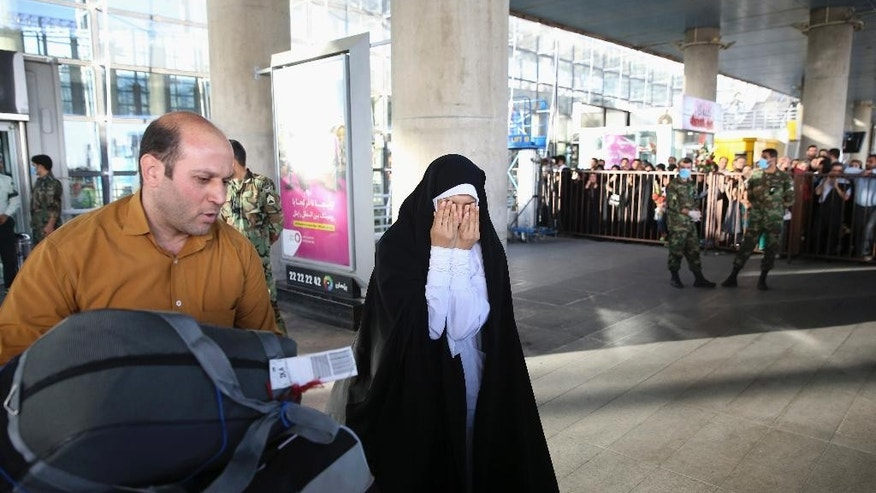 A female Iranian hajj pilgrim gets emotional upon her relative's arrival at Tehran Imam Khomeini airport, Iran, Tuesday, Sept. 29, 2015. More than 700 pilgrims were killed on Thursday in a stampede during the final days of the annual hajj in Mina near the holy city of Mecca, Saudi Arabia. The disaster killed at least 239 Iranian pilgrims, while over 200 people remain missing, Iran's state television reported. (AP Photo/Vahid Salemi)