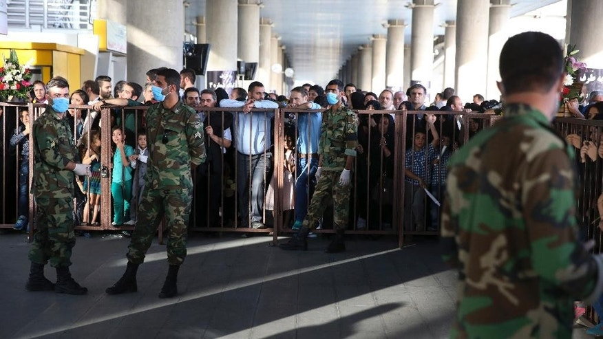 Iranian police officers control the scene where people wait to welcome their relatives from the hajj pilgrimage in Saudi Arabia, at Tehran Imam Khomeini airport, Iran, Tuesday, Sept. 29, 2015. More than 700 pilgrims were killed last Thursday in a deadly stampede during the final days of the annual hajj in Mina, near the holy city of Mecca in Saudi Arabia. The disaster killed at least 239 Iranian pilgrims, while 241 remain missing, state television reported. (AP Photo/Vahid Salemi)