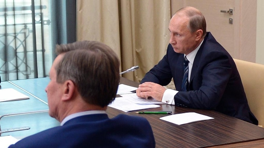 Russian President Vladimir Putin, right, holds a meeting with senior government officials at the Novo-Ogaryovo residence outside Moscow, Russia on Wednesday, Sept. 30, 2015. Russian military jets carried out airstrikes against the Islamic State group in Syria on Wednesday for the first time, after President Vladimir Putin received parliamentary approval to send Russian troops to Syria.  (Alexei Nikolsky/RIA Novosti, Kremlin Pool Photo via AP)