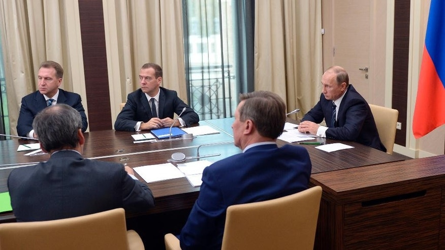 Russian President Vladimir Putin, right, holds a meeting with senior government officials at the Novo-Ogaryovo residence outside Moscow, Russia on Wednesday, Sept. 30, 2015. Russian military jets carried out airstrikes against the Islamic State group in Syria on Wednesday for the first time, after President Vladimir Putin received parliamentary approval to send Russian troops to Syria. Background from left: Igor Shuvalov, first deputy premier, Dmitry Medvedev, Premier. (Alexei Nikolsky/RIA Novosti, Kremlin Pool Photo via AP)