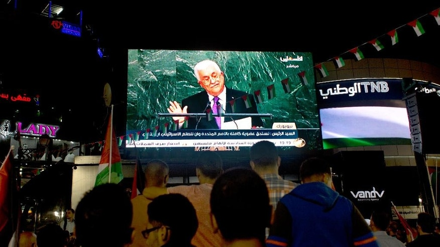 Palestinians watch a speech by Palestinian President Mahmoud Abbas at the U.N. General Assembly shown on TV in the West Bank city of Ramallah, Wednesday, Sept. 30, 2015. Abbas declared before world leaders Wednesday that he is no longer bound by agreements signed with Israel, and called on the United Nations to provide international protection for the Palestinian people. (AP Photo/Nasser Nasser)