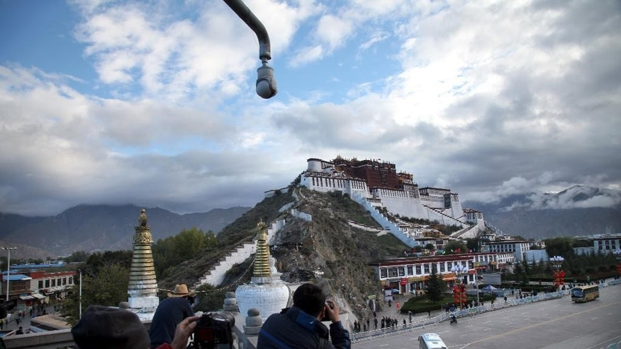 In this Saturday, Sept. 19, 2015 photo, tourists take photos of the Potala Palace beneath a security camera in Lhasa, capital of the Tibet Autonomous Region of China. Top-down development has poured more than $100 million dollars into the region since 1952, but critics say that Beijing's obsession with social stability also has led to widespread human right abuses. (AP Photo/Aritz Parra)