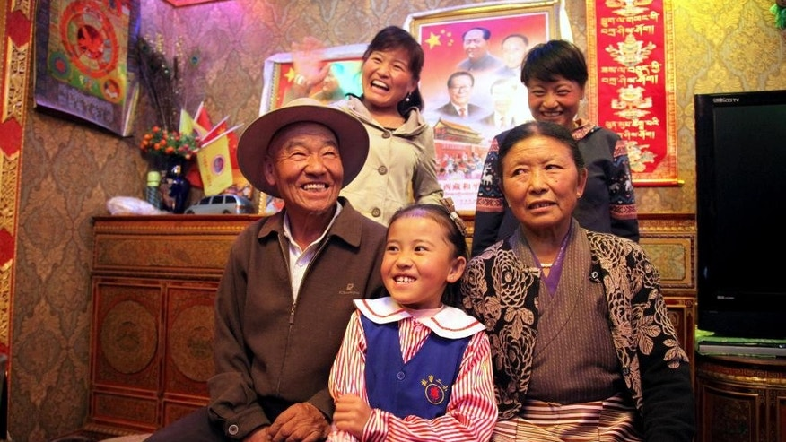 In this Thursday, Sept. 17, 2015 photo, three generations of Tibetans pose for a photo at the home of Lhamu Tseren, 63, seated at right, and Dronjie, 69, seated at left, during a visit by local Communist Party cadres and journalists to their home in Lhasa, capital of the Tibet Autonomous Region of China. As incomes finally begin to increase across the Tibetan countryside, Chinese authorities are hopeful they can dispel international criticism over their rule in Tibet while winning the hearts of Tibetans and pulling some of their loyalty away from the exiled Dalai Lama. (AP Photo/Aritz Parra)