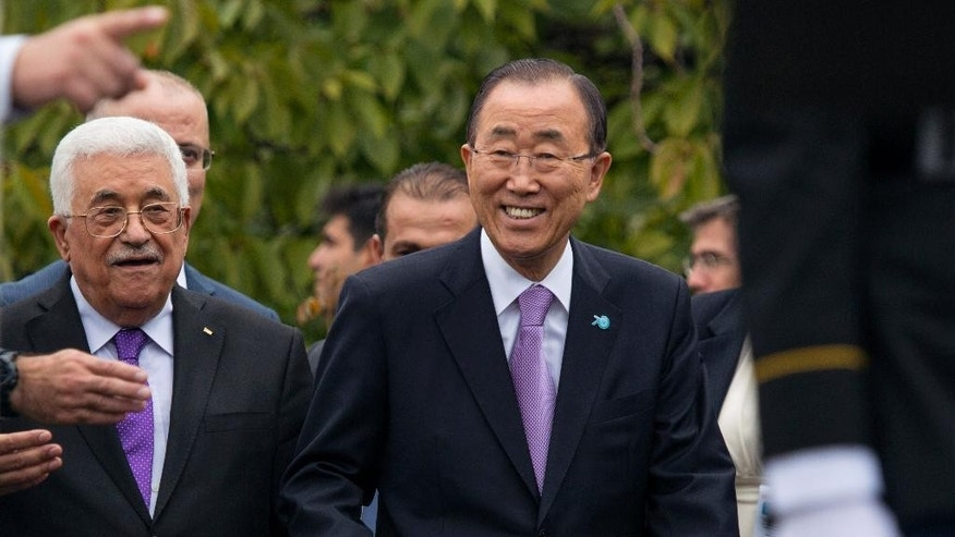Mahmoud Abbas, left, president of the State of Palestine, walks with United Nations Secretary-General Ban Ki-moon during a ceremony to raise the State of Palestine flag for the first time on Wednesday, Sept. 30, 2015, at the U.N. (AP Photo/Craig Ruttle)
