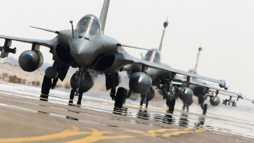 This photo released on Sunday, Sept. 27, 2015 by the French Army Communications Audiovisual office (ECPAD) shows French army Rafale fighter jets on the tarmac of an undisclosed air base as part of France's Operation Chammal launched in September 2015 in support of the US-led coalition against Islamic State group. Six French jet fighters targeted and destroyed an Islamic State training camp in eastern Syria in a five-hour operation on Sunday, President Francois Hollande announced, making good on a promise to go after the group that he has said is planning attacks against several countries, including France. (French Army/ECPAD via AP) THIS IMAGE MAY ONLY BE USED FOR 30 DAYS FROM TIME TRANSMISSION.