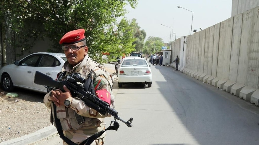 An Iraqi soldier stands guard while released Turkish workers arrive to the Turkish embassy in Baghdad, Iraq, Wednesday, Sept. 30, 2015. Sixteen Turkish workers kidnapped from a construction site in Baghdad and held for nearly a month were released on Wednesday, Turkey's prime minister and Iraqi officials said. (AP Photo/Karim Kadim)