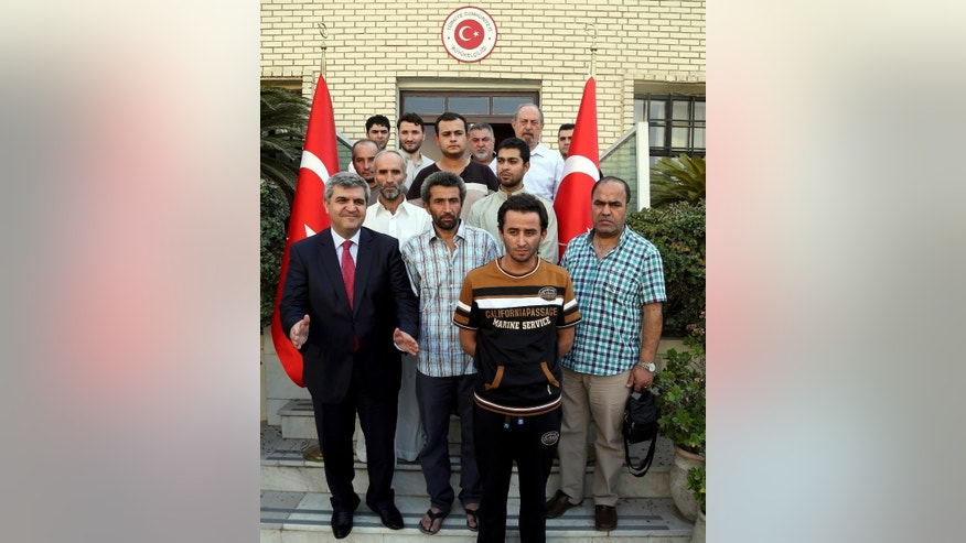 Released Turkish workers attend a press conference held by Turkish Ambassador to Iraq, Faruk Kaymakci, left, at Turkish embassy, Baghdad, Iraq, Wednesday, Sept. 30, 2015. Sixteen Turkish workers kidnapped from a construction site in Baghdad and held for nearly a month were released on Wednesday, Turkey's prime minister and Iraqi officials said. (AP Photo/Karim Kadim)
