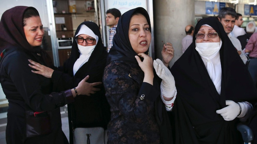 Sept. 29, 2015: A female Iranian hajj pilgrim, right, weeps as she and her travel companion, second left, are welcomed by their relatives upon arrival at Tehran Imam Khomeini airport, Iran.