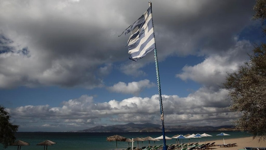 A Greek tattered flag flutters at Agios Prokopios beach on the Greek Aegean island of Naxos, Greece, Oct 1, 2015. For decades, Greece's Aegean islands enjoyed a value added tax rate 30 percent lower than the rest of the country, to offset increased transportation costs and prevent their dwindling permanent populations from deserting them altogether, but now the islands are losing that benefit as part of creditor-demanded reforms for Greece's third international bailout. (AP Photo/Yorgos Karahalis)
