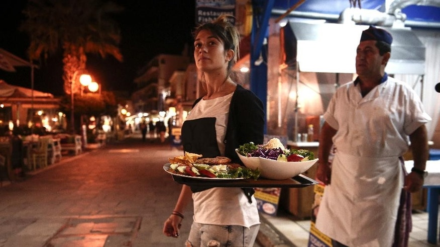 In this photo taken Sept. 30, 2015, a waitress carries dishes outside a restaurant on the Greek Aegean island of Naxos. For decades, Greece's Aegean islands enjoyed a value added tax rate 30 percent lower than the rest of the country, to offset increased transportation costs and prevent their dwindling permanent populations from deserting them altogether, but now the islands are losing that benefit as part of creditor-demanded reforms for Greece's third international bailout.  (AP Photo/Yorgos Karahalis)