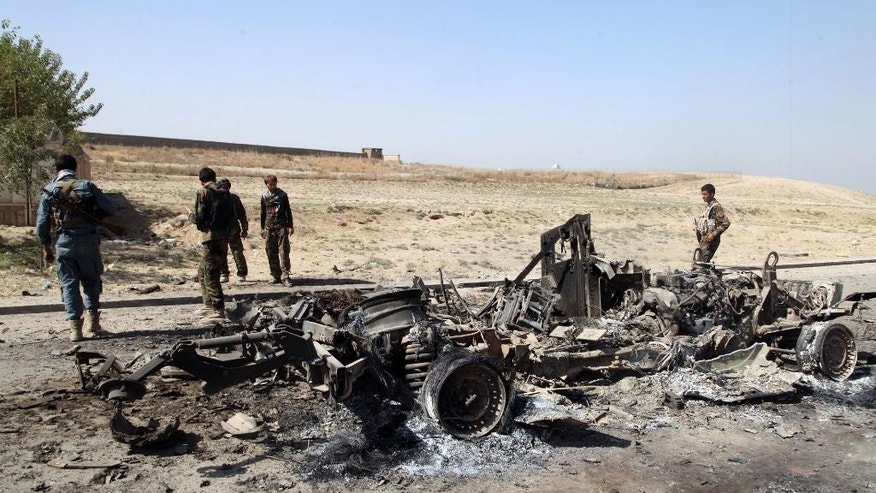 "Afghan security personnel walk around a burnt out vehicle near Kunduz city, north of Kabul, Afghanistan, Thursday, Oct. 1, 2015. An Afghan official says government forces have retaken the strategic northern city of Kunduz, which was seized by the Taliban on Monday. The spokesman says it could take some days to ""clear the city,"" but that Taliban forces have retreated. He says about 200 Taliban fighters have been killed. (AP Photo)"