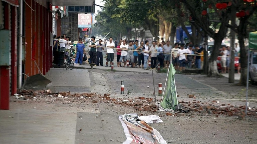 Spectators stand at the scene of an explosion in Liucheng county in southern China's Guangxi Zhuang Autonomous Region Thursday, Oct. 1, 2015. An explosion damaged a six-story building Thursday in southern China, less than a day after more than a dozen blasts triggered by explosive devices delivered in mail packages killed several people and injured dozens more in the same county in southern China, officials and state media said. (Chinatopix Via AP) CHINA OUT