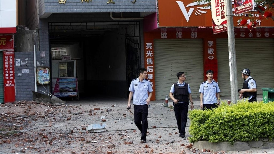 Chinese police officers walk past the scene of an explosion in Liucheng county in southern China's Guangxi Zhuang Autonomous Region Thursday, Oct. 1, 2015. An explosion damaged a six-story building Thursday in southern China, less than a day after more than a dozen blasts triggered by explosive devices delivered in mail packages killed several people and injured dozens more in the same county in southern China, officials and state media said. (Chinatopix Via AP) CHINA OUT