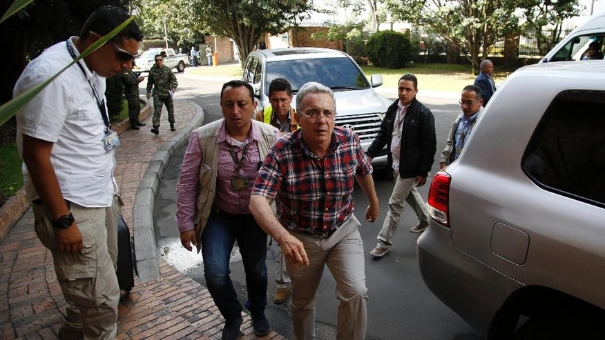 Surrounded by bodyguards Colombia´s Senator and former President Alvaro Uribe, center, arrives to a hotel for an interview with The Associated Press in Bogota, Colombia, Thursday, Oct. 1, 2015. Uribe has been critical of the agreements reached by President Juan Manuel Santos and rebel leaders in Havana. (AP Photo/Fernando Vergara)