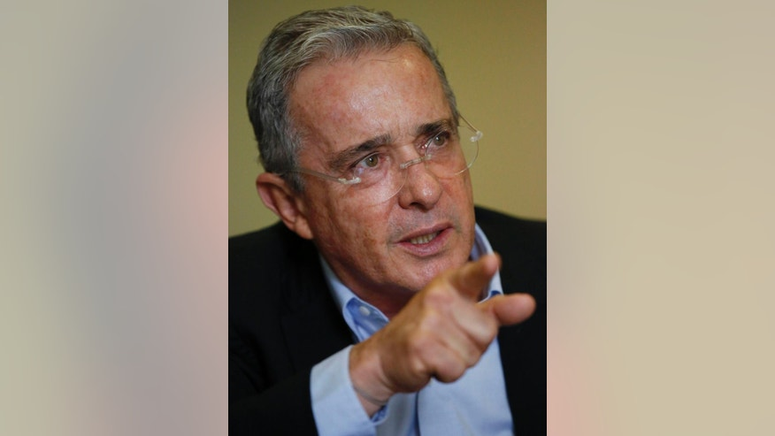 Colombia´s Senator and former President Alvaro Uribe gestures during an interview with The Associated Press in Bogota, Colombia, Thursday, Oct. 1, 2015. Uribe lashed out at what he considers a double standard by the international community for applauding a recent breakthrough in peace talks with leftist rebels that he says puts the country on a path toward more violence and impunity.  (AP Photo/Fernando Vergara)